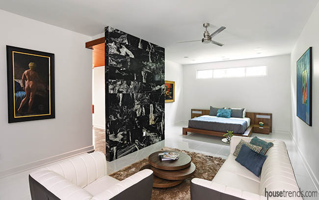 Black granite visually connects a master bedroom and bath