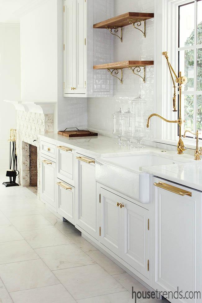 Brass hardware pops in a white kitchen design