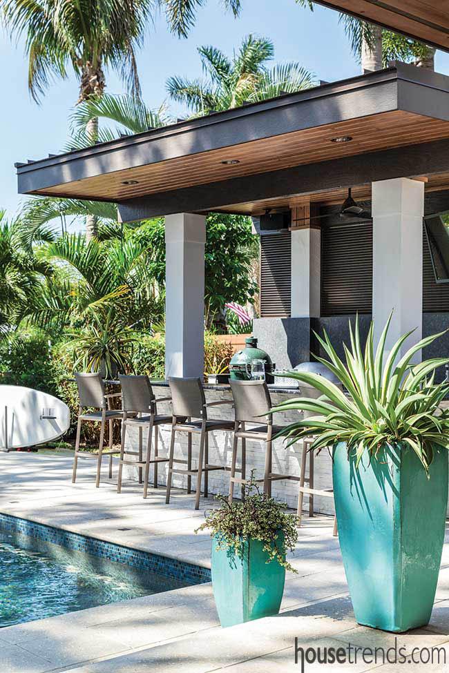 Bar stools surround an outdoor kitchen