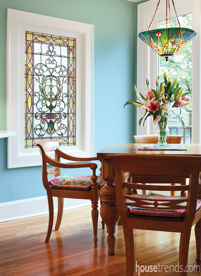 Colorful chandelier complements a stained glass window