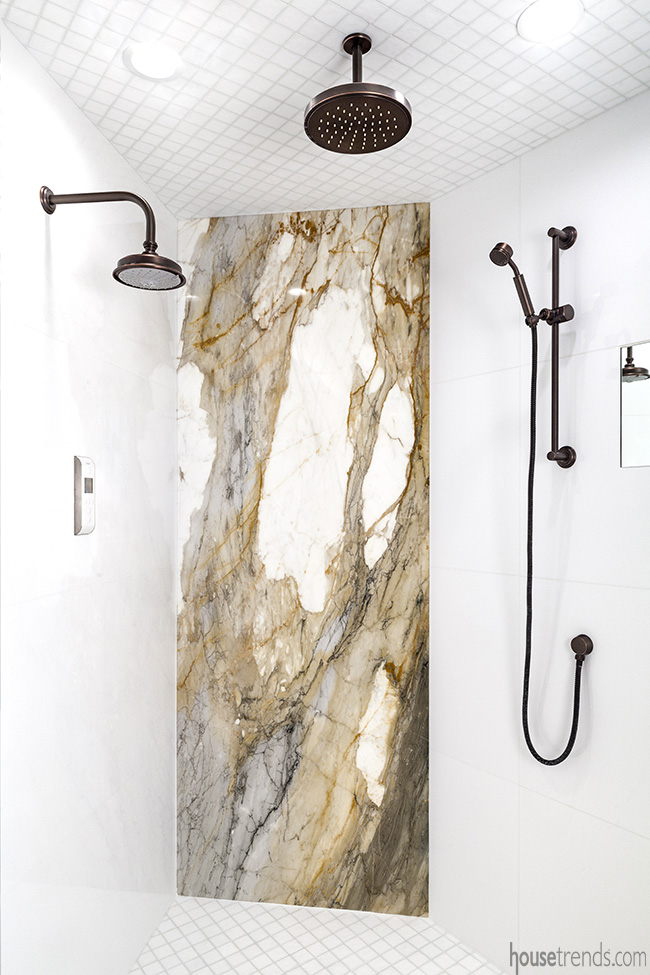 A dark bronze rain showerhead hangs from the ceiling in this bathroom remodel.