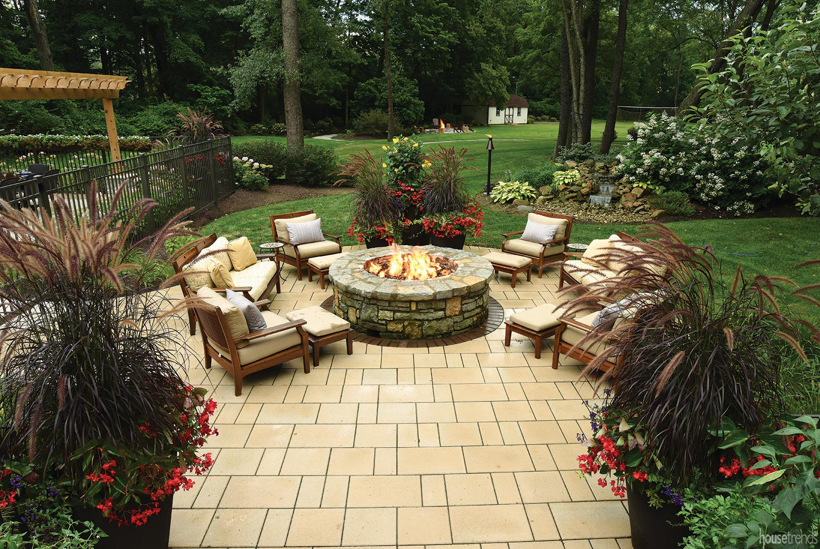 Cushioned chairs surround a gas fire pit