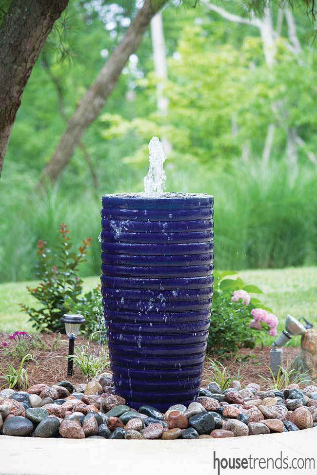 Decorative rocks surround a blue fountain