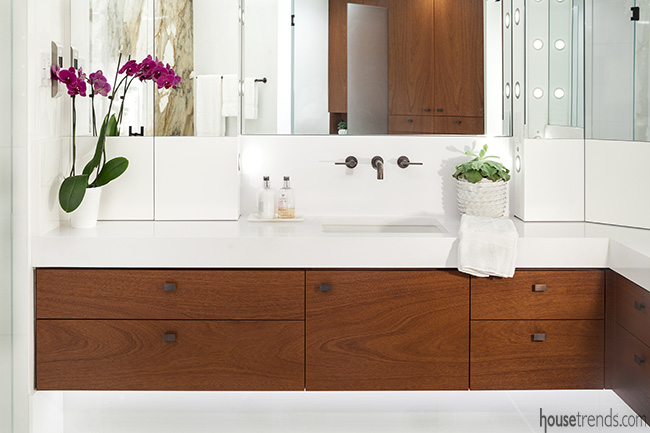 Thick white quartz counters top the mahogany floating vanities in this bathroom remodel.
