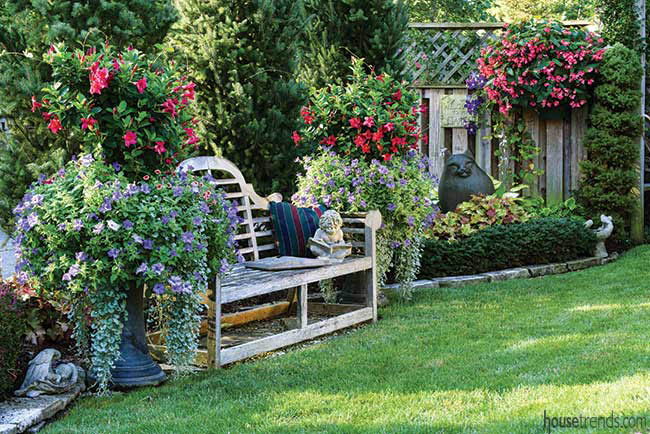 Garden bench flanked by colorful flowers