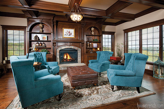 Teal armchairs pop in a cozy hearth room