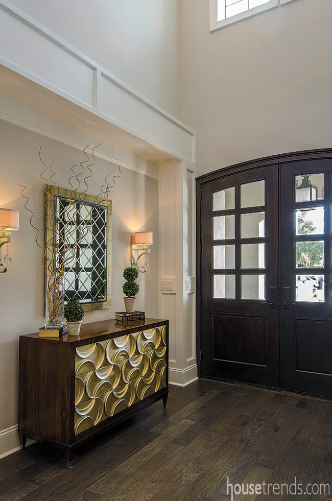 Interior decorating ideas for the foyer include wall sconces and a mirror