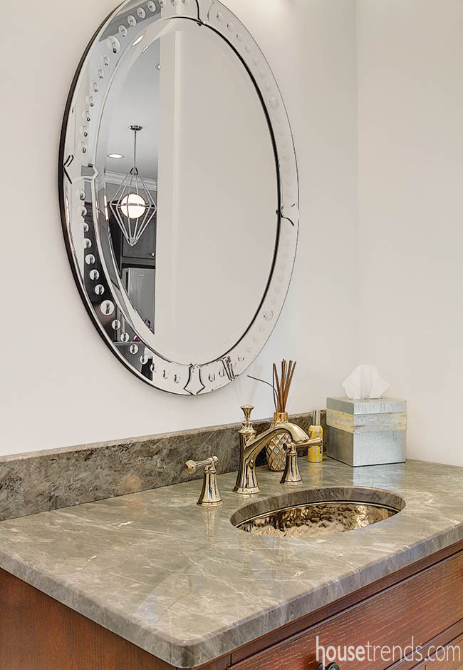 Oval mirror and hammered sink add texture to a powder room