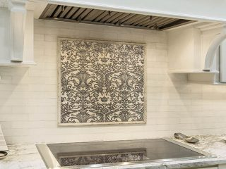 Backsplash design complements a sleek cooktop