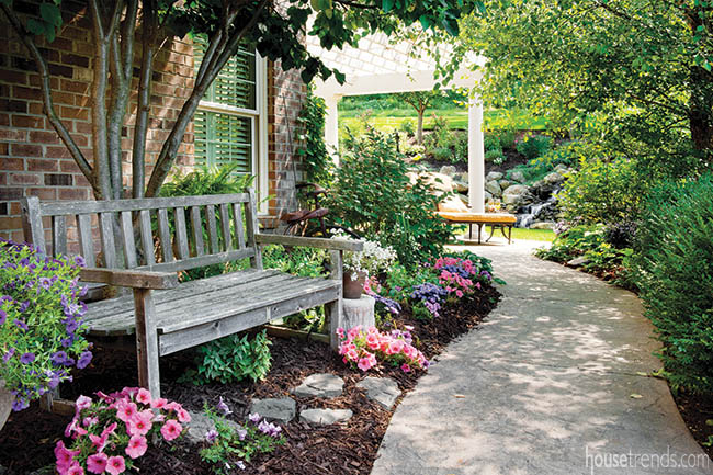 Colorful blooms surround a garden bench