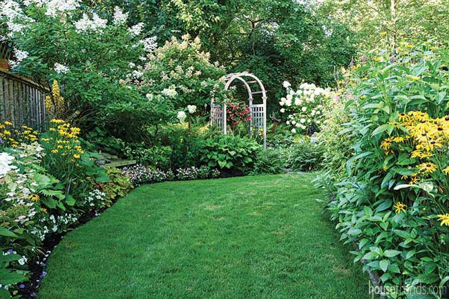 Perennials and annuals surround an arbor