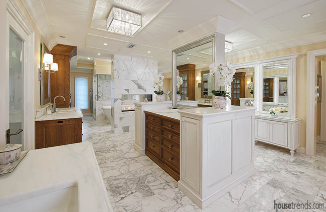 Double-sided fireplace heats up a master bathroom design