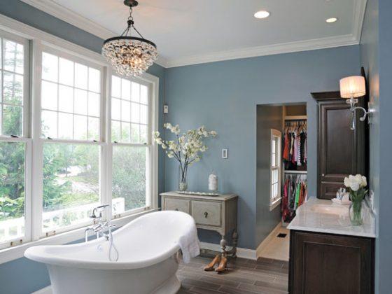 A freestanding cast bathtub sits beneath a leaded-glass chandelier.