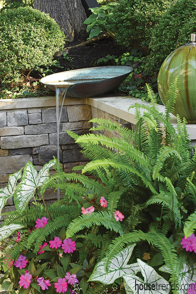 Water feature tops off a retaining wall