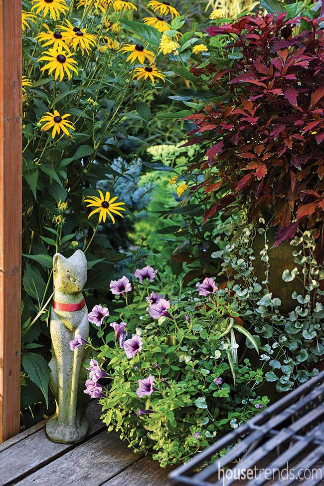 Cat statue sits among garden flowers