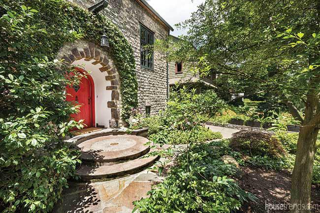 Red door lends a magical feel to a garden