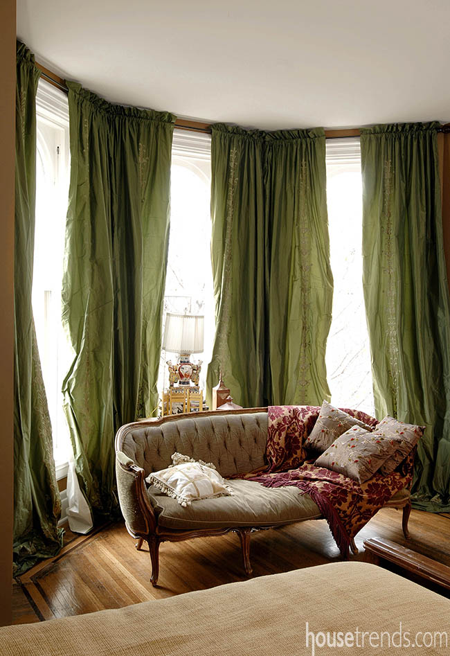 Green drapes color up a bedroom sitting area