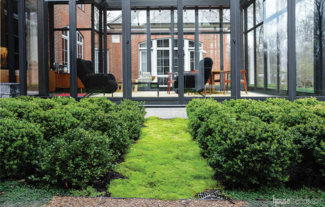 Scotch moss creates a pathway off of a glass house