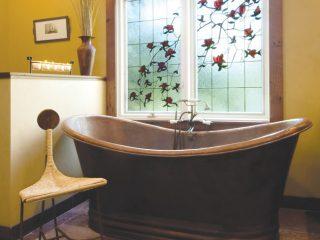 Bath tub and window give off a regal feel