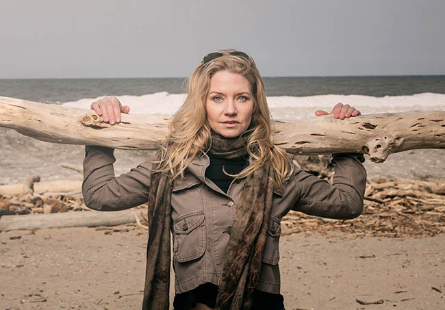 Designer poses with driftwood