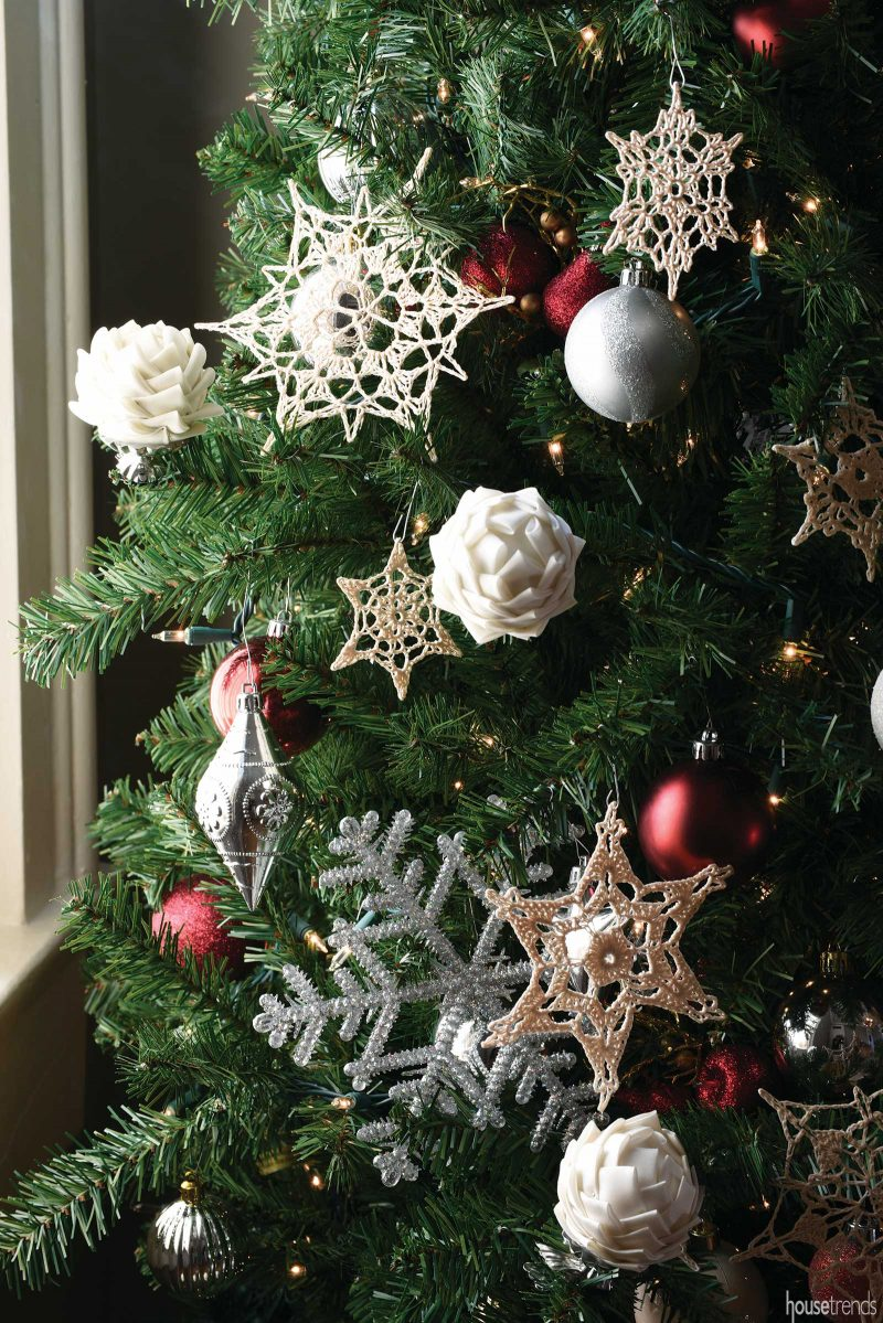 Hand-made ornaments and pinecones adorn the tree.